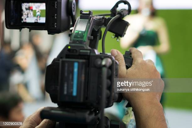 man filming people through television camera.videoand shoot video concept. - film director stock pictures, royalty-free photos & images