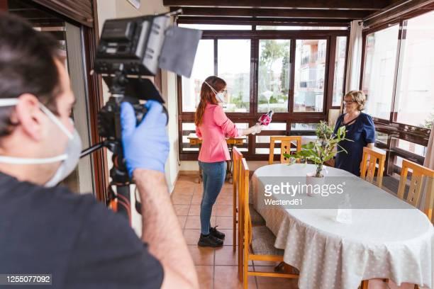 man filming reporter interviewing senior woman at home - 報導式影象 個照片及圖片檔