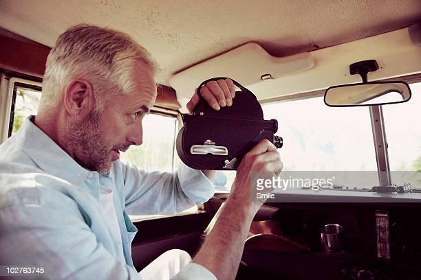 Man filming through off road vehicle's window
