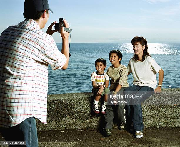 Man filming woman and two sons (5-10) sitting on rock wall beside sea