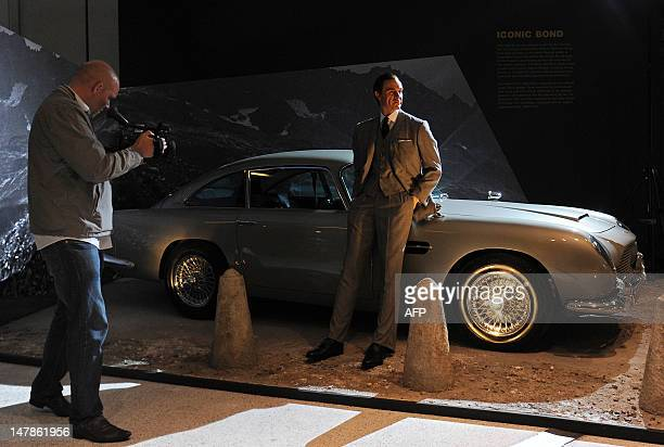 A man films a replica of the Aston Martin car used in the James Bond film 'GoldenEye' during a press preview for an exhibition entitled 'Designing...