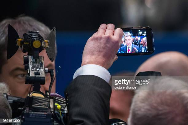 A man films an interview with Bavarian Finance Minister Markus Soeder on his mobile phone at the CSUparty conference in Nuremberg Germany 15...