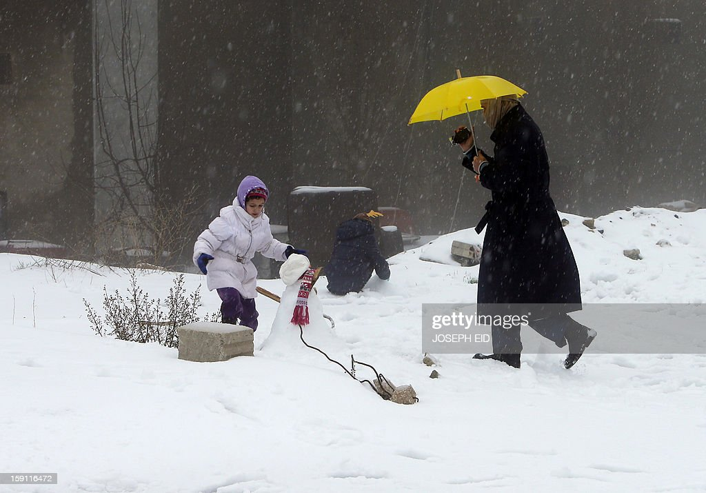 A man films his children as they play with snow in the Lebanese village of Bhamdun, east of Beirut, on January 8, 2013. Stormy weather, including high winds and heavy rainfall, lashed the eastern Mediterranean coast, downing power lines and trees and causing several injuries in a number of countries.