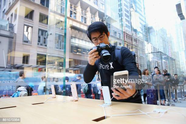 A man films product inside as people queue outside for the release of the iPhone 8 and 8 Plus at Apple Store on September 22 2017 in Sydney Australia...