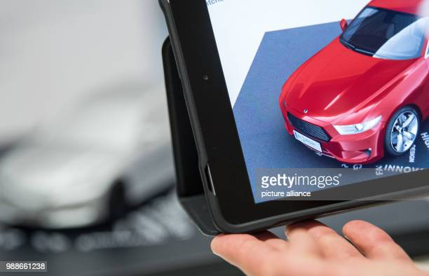 A man films the model of a car in order to change its colour via augmented reality on a tablet in Stuttgart Germany 29 November 2017 Photo Sebastian...