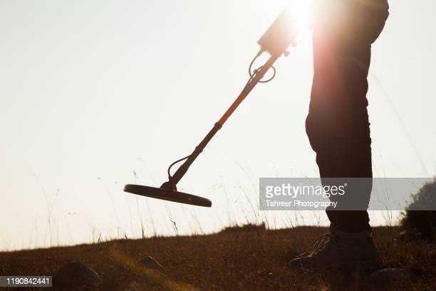 a man finding treasure using metal detector - treasuregold stock pictures, royalty-free photos & images