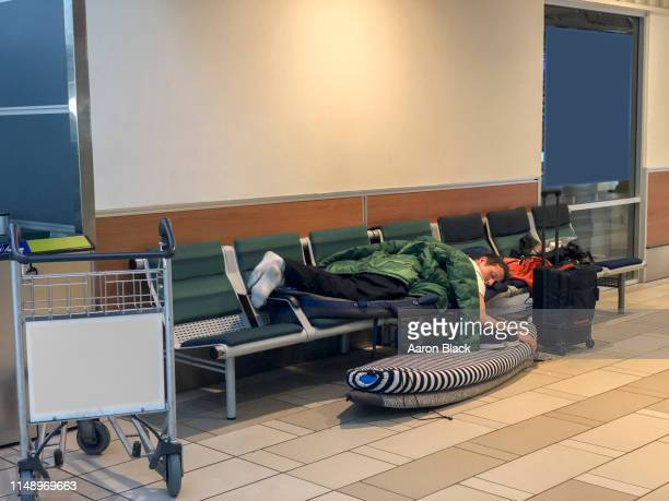 man finds comfort sleeping on a bench in an airport. - vancouver international airport stock pictures, royalty-free photos & images