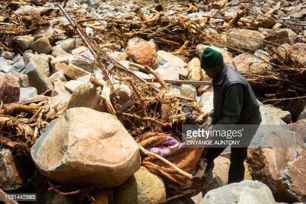 A man finds his blanket among debris while looking for his missing daughter in Ngangu township Chimanimani Manicaland Province eastern Zimbabwe on...