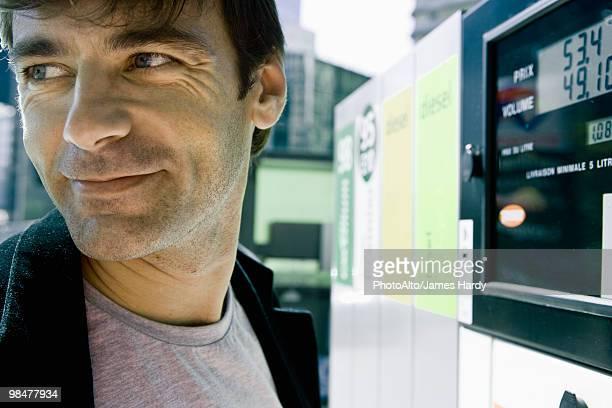 Man finishing at gas pump preparing to leave