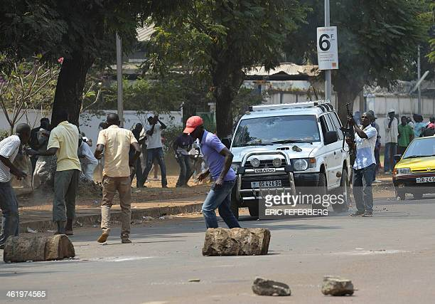 A man fires a gun into the air to protect a car transporting two children of an exSeleka colonel at the 'UN crossroad'' on January 12 2014 In Bangui...