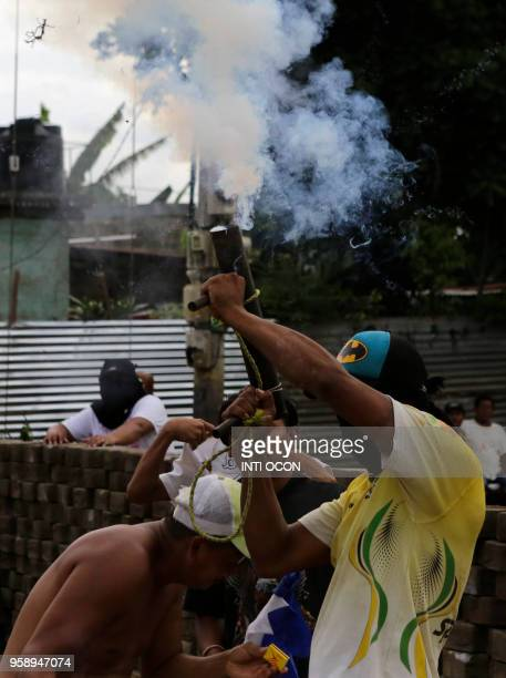 A man fires a handmade mortar during protests in Masaya some 40km southeast of Managua on May 15 2018 Nicaragua's powerful Roman Catholic bishops...