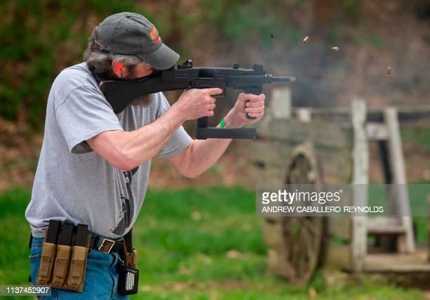 A man fires an Uzi in a submachine gun shooting competition during the Knob Creek Machine Gun Shoot and Military Gun show in Bullitt County near West...