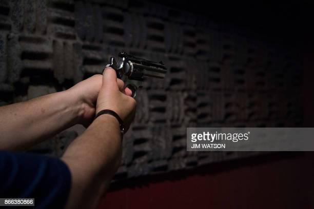 A man fires his 357 revolver at the Lynchburg Arms Indoor Shooting Range in Lynchburg Virginia on October 20 2017 Virginia residents go to the polls...