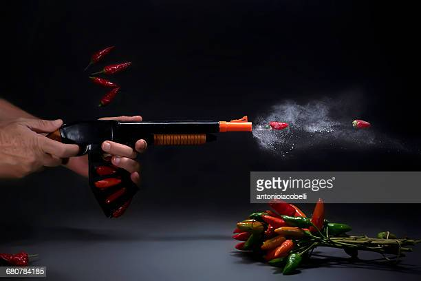 Man firing toy gun with chillis and baby powder