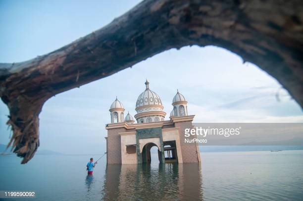 A man fished near a floating mosque that collapsed into the sea on the coast of Kampung Lere Palu Central Sulawesi Indonesia on February 9 2020 The...