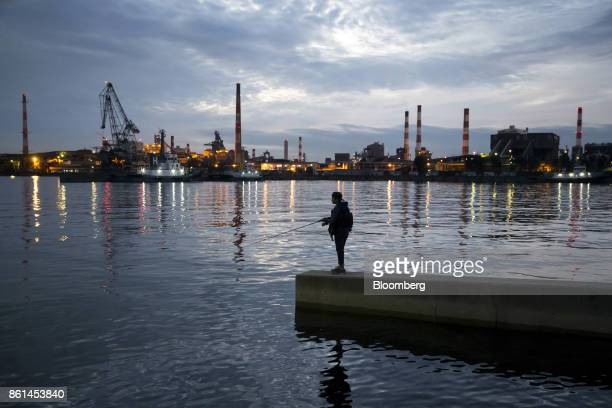 A man fishes along a promenade as a Kobe Steel Ltd plant stands illuminated in the background a dusk in Kakogawa Hyogo Japan on Saturday Oct 14 2017...