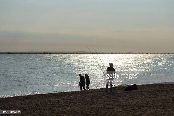A man fishes as a couple walk along the beach while the sun goes down during recent warm weather on September 20 2020 in Southend on Sea London