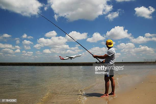 A man fishes as an Airbus A330300 aircraft operated by Qantas Airways Ltd takes off from Sydney Airport in Sydney Australia on Monday Feb 22 2016...