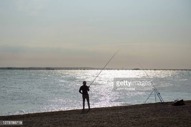 A man fishes as the sun goes down during recent warm weather on September 20 2020 in Southend on Sea London