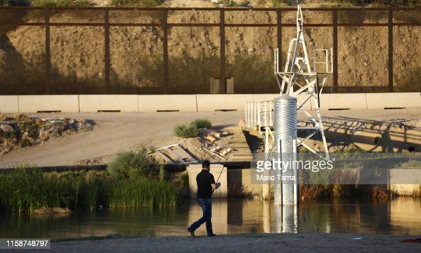 A man fishes at the Rio Grande river with the USMexico border barrier in the background on June 27 in Ciudad Juarez Mexico According to US Customs...