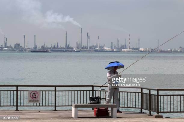 A man fishes before the Shell petroleum refinery on Bukom island in Singapore on January 9 2018 Singaporean authorities have arrested 17 men for...
