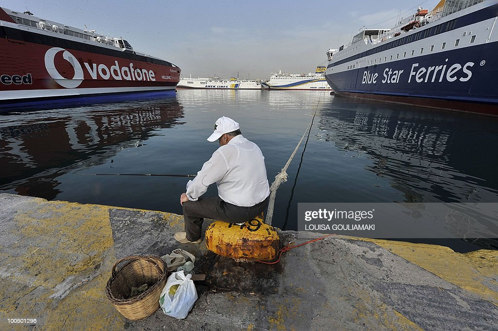 A man fishes by docked ferries in the port of Piraeus due to a 24-hours strike on May 5, 2010. A nationwide general strike gripped Greece in the first major test of the socialist government's resolve to push through unprecedented austerity cuts needed to avert fiscal meltdown. AFP PHOTO / Louisa Gouliamaki