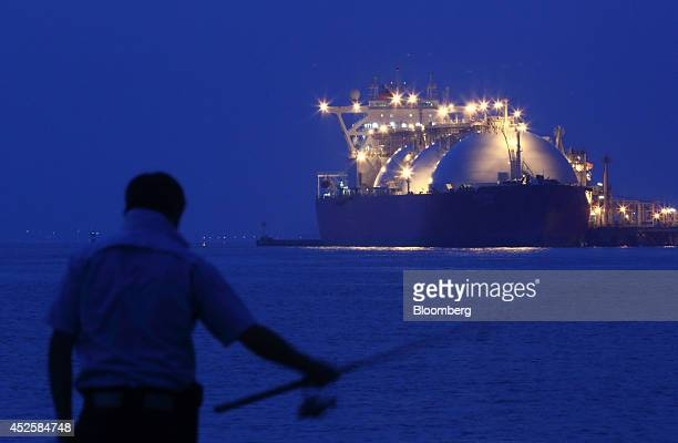 A man fishes in front of a liquefied natural gas tanker berthed at Tokyo Electric Power Co's Futtsu gasfired thermal power plant at night in Futtsu...