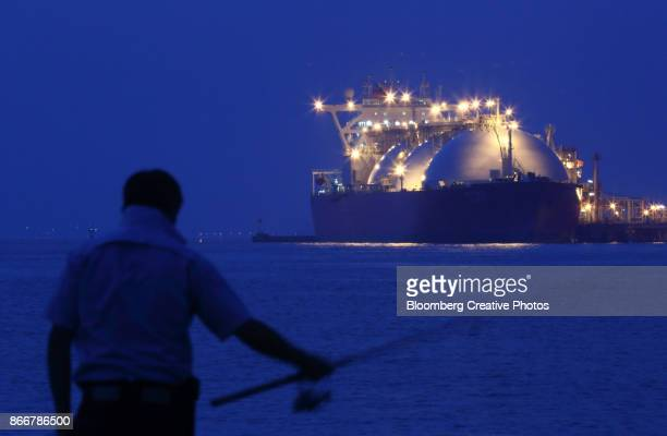 A man fishes in front of a liquefied natural gas (LNG) tanker