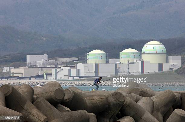 A man fishes in front of Hokkaido Electric Power Co's Tomari nuclear power plant in Tomari Village Hokkaido Japan on Sunday May 6 2012 Japan began a...