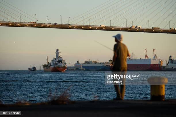 A man fishes in front of ships at a port in Nagoya Japan on Tuesday July 31 2018 Japan is scheduled to release trade balance figures for July on Aug...