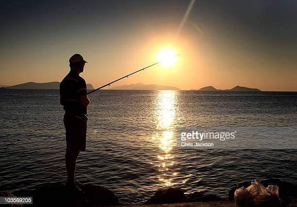 A man fishes in the bay on the island of Spetses on August 24 2010 in Spetses Greece The small Greek Island three hours from Athens is gearing up for...