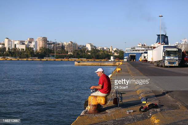 A man fishes in the harbour at Piraeus the Port of Athens on June 14 2012 in Athens Greece The Greek electorate are due to go to the polls in a rerun...