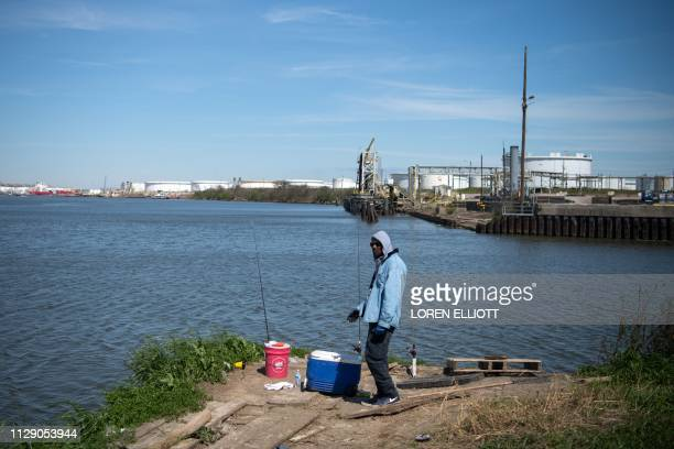 A man fishes in the Houston Ship Channel part of the Port of Houston on March 6 in Pasadena Texas