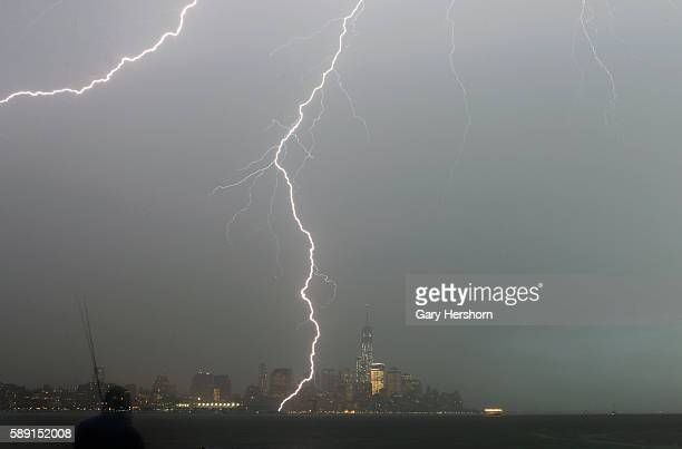 A man fishes in the Hudson River as a bolt of lightning hits the ground next to One World Trade Center in Lower Manhattan as an electrical storm...