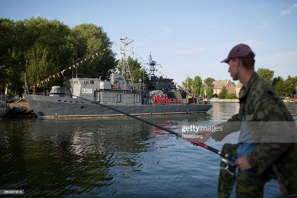 A man fishes near a Russian naval warship at its moorings during Russian Navy day at the Vistula lagoon in Baltiysk, Russia, on Sunday, July 31, 2016. Amid Russia's recent rearmament, the Kaliningrad region has increasingly returned to its Soviet-era role as a garrison on the strategic Baltic Sea coast. Photographer: Andrey Rudakov/Bloomberg via Getty Images
