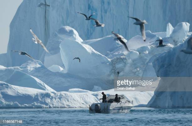Man fishes near icebergs in the Ilulissat Icefjord on August 04, 2019 in Ilulissat, Greenland. As the Earth's climate warms summers have become...