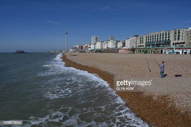 A man fishes on an otherwise empty beach in Brighton southern England on March 24 2020 after Britain ordered a lockdown to slow the spread of the...