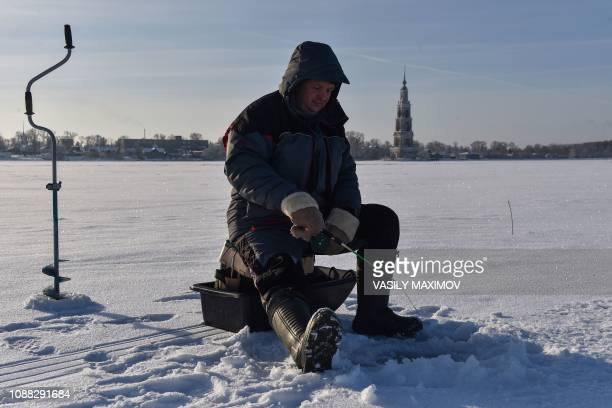 TOPSHOT A man fishes on the icecovered Volga river with the belfry of the St Nicholas Cathedral seen in the background in the town of Kalyazin in...