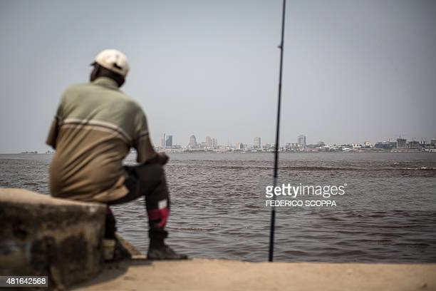 A man fishes on the shores of the Congo river in Brazzaville on July 22 whereas on the other side of the river the capital of the Democratic Republic...