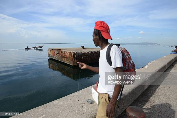 A man fishes on the waterfront in Kingston as Jamaica braces for Hurricane Matthew on October 2 2016 Hurricane Matthew the most powerful Caribbean...