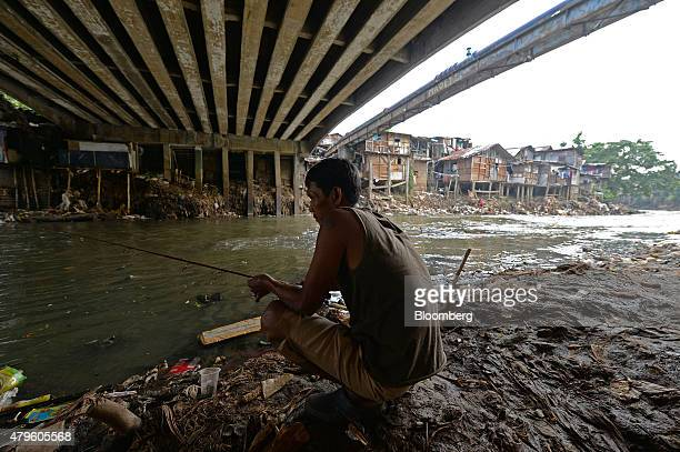 A man fishes under a bridge near shanty houses standing perched on stilts along a river in Jakarta Indonesia on Tuesday June 23 2015 Having watched...