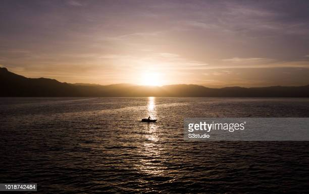 A man fishes under the warm light of sunrise at Lake Atitlan on 12 August 2018 in Guatemala Central America