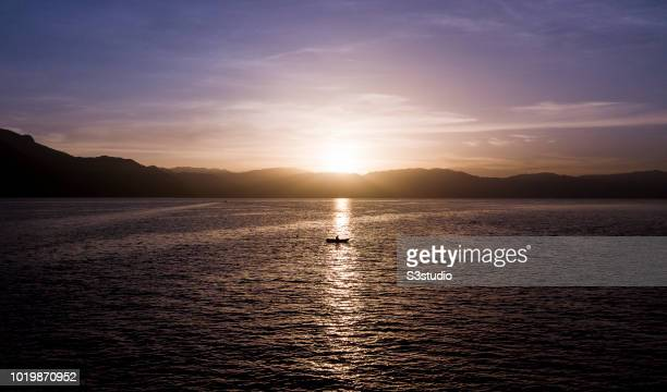 A man fishes under the warm light of sunrise at Lake Atitlan on 12 August 2018 in the Solola department Guatemala Central America