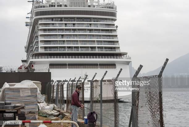 A man fishes while behind stands at large the Dream World cruiser docking at Kai Tak Cruise Terminal in Kowloon Bay Hong Kong in Kowloon Bay Hong...