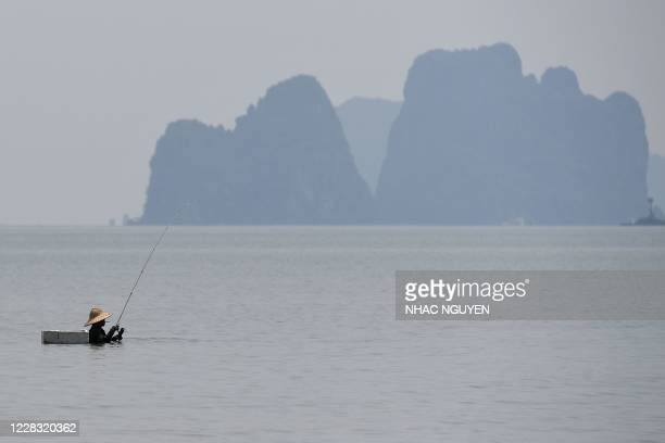 TOPSHOT A man fishes while standing the water of Halong bay in Quang Ninh province on September 3 2020