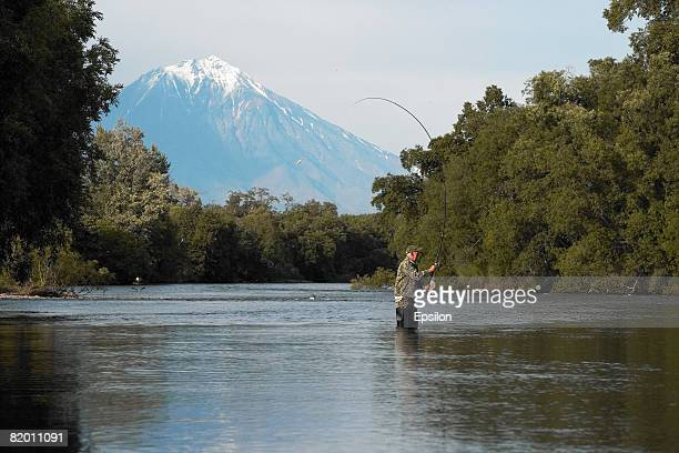A man fishes with Vilyuchinskaya sopka volcano in the background on August 19 2007 in Kamchatka Russia Kamchatka has the highest density of volcanos...