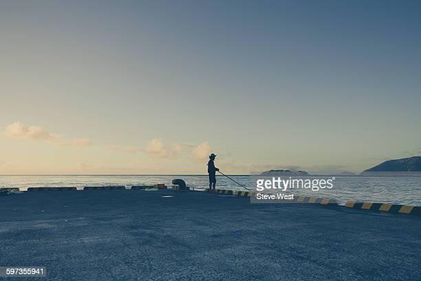 Man fishing alone at sunset