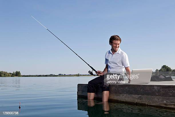 Man fishing and using laptop on dock