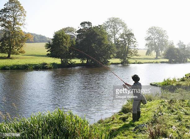 Man fishing at edge of lake.