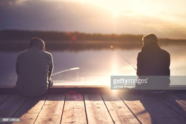 man fishing at lake - jetty stock pictures, royalty-free photos & images